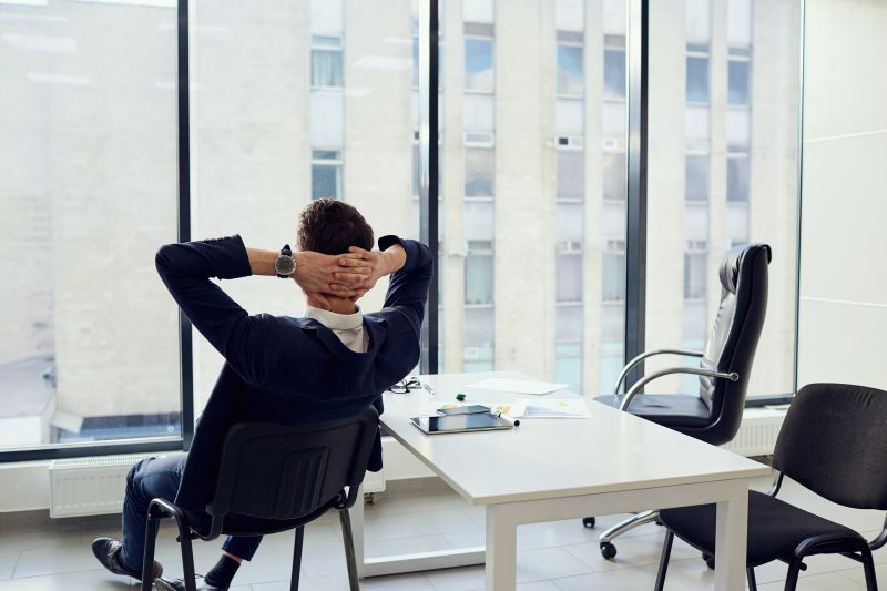Muž v kanceláři s rukama za hlavou